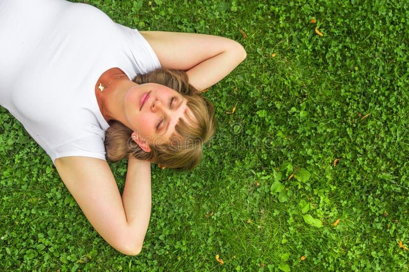 Γυναίκα που χαλαρώνει υπαίθρια και που βρίσκεται στη χλόη στο πάρκο στοκ φωτογραφία με δικαίωμα ελεύθερης χρήσης