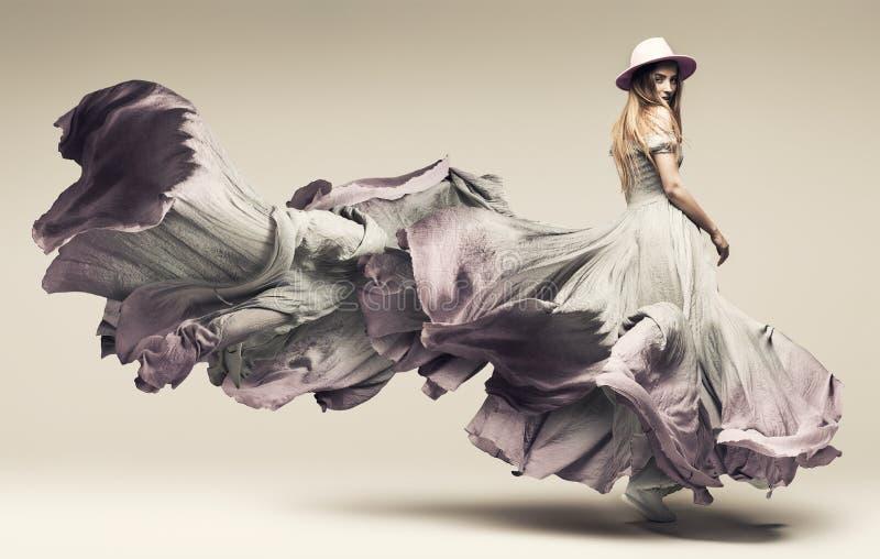 Γυναίκα που χορεύει στο κυματίζοντας πορφυρά φόρεμα και το καπέλο στοκ εικόνες