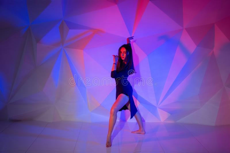 Γυναίκα που χορεύει στο υπόβαθρο ενός όμορφου πολύχρωμου τοίχου Προκλητικό λεπτό μόνο κορίτσι με τη μακριά μαύρη τρίχα στο α στοκ φωτογραφία