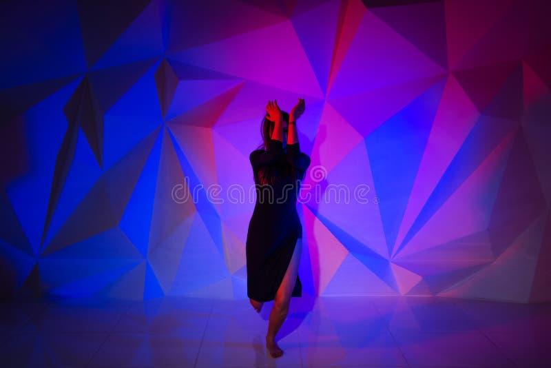 Γυναίκα που χορεύει στο υπόβαθρο ενός όμορφου πολύχρωμου τοίχου Προκλητικό λεπτό μόνο κορίτσι με τη μακριά μαύρη τρίχα στο α στοκ εικόνες με δικαίωμα ελεύθερης χρήσης