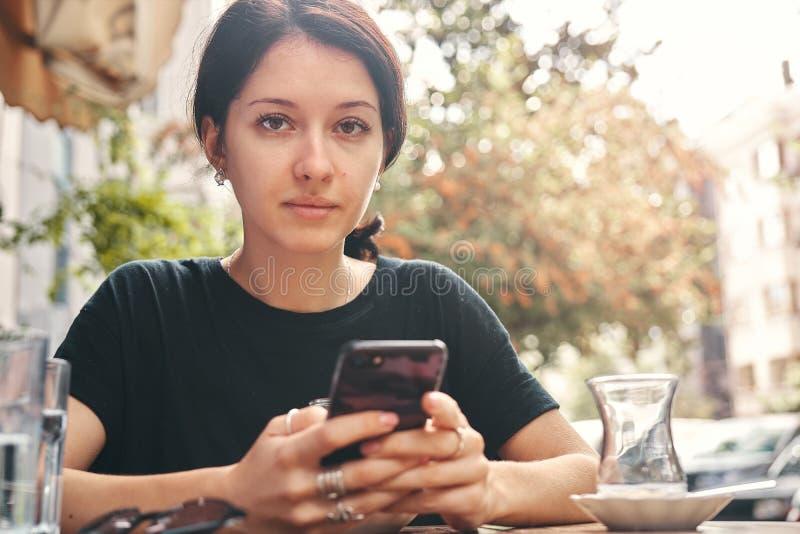 Γυναίκα που χρησιμοποιεί ένα κινητό τηλέφωνο στον καφέ με το διάστημα αντιγράφων στοκ εικόνες