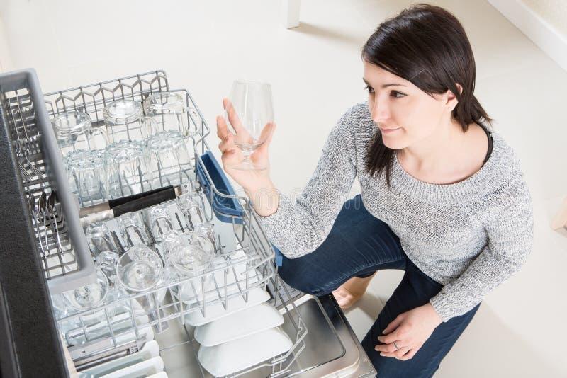Γυναίκα που χρησιμοποιεί ένα πλυντήριο πιάτων σε μια σύγχρονη κουζίνα στοκ φωτογραφίες με δικαίωμα ελεύθερης χρήσης