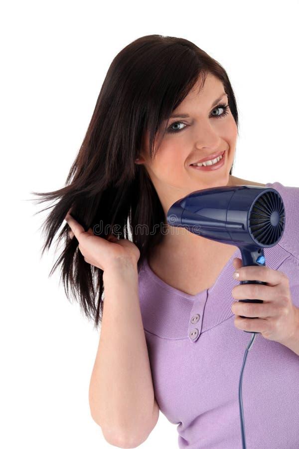 Γυναίκα που χρησιμοποιεί ένα Hairdryer Στοκ Εικόνα