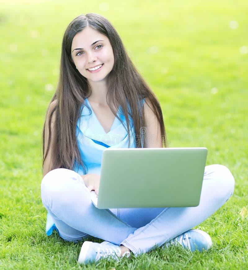 Γυναίκα που χρησιμοποιεί ένα lap-top υπαίθρια στοκ εικόνα