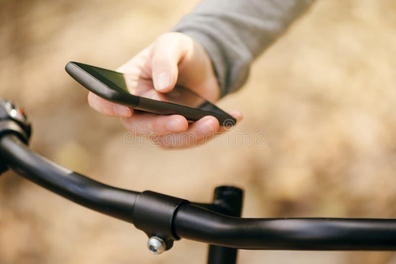 Γυναίκα που χρησιμοποιεί έξυπνο app στο τηλέφωνο οδηγώντας το ποδήλατο στοκ εικόνες