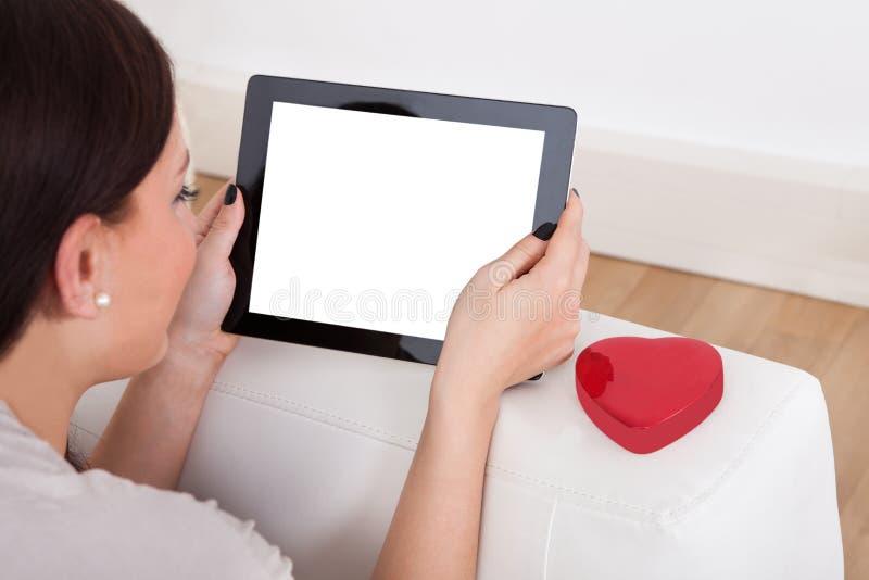 Γυναίκα που χρησιμοποιεί την ψηφιακή ταμπλέτα για on-line να χρονολογήσει στοκ φωτογραφία