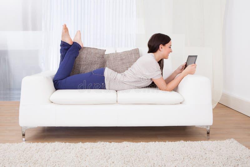 Γυναίκα που χρησιμοποιεί την ψηφιακή ταμπλέτα στον καναπέ στοκ εικόνες