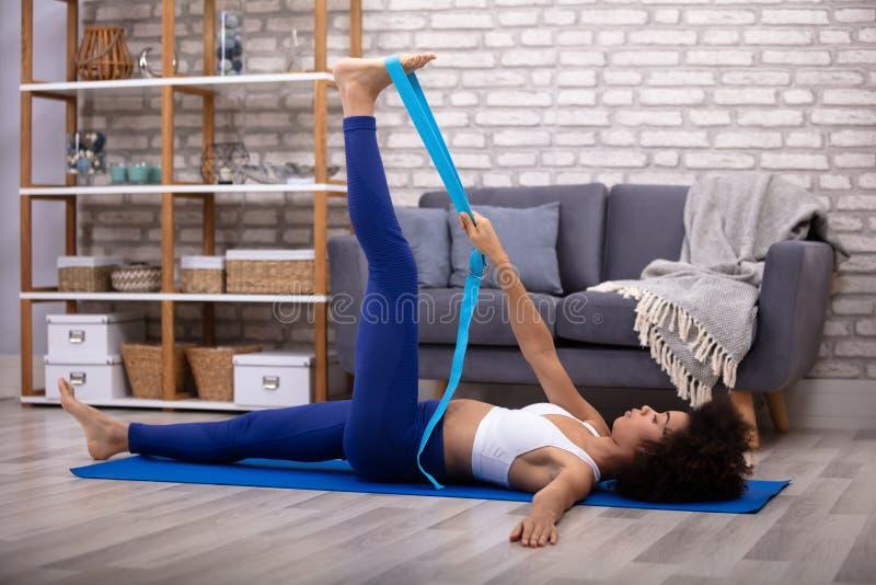 Γυναίκα που χρησιμοποιεί τη ζώνη γιόγκας κάνοντας την άσκηση στοκ εικόνες με δικαίωμα ελεύθερης χρήσης
