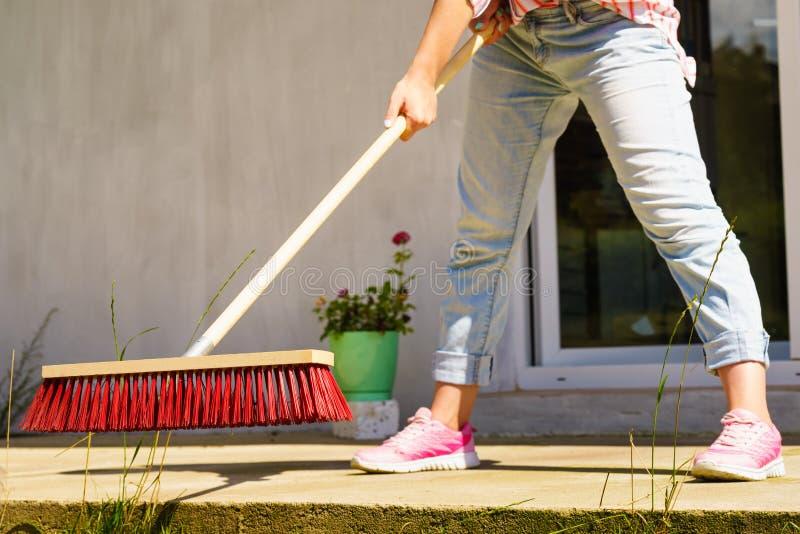 Γυναίκα που χρησιμοποιεί τη σκούπα για να καθαρίσει επάνω το patio κατωφλιών στοκ φωτογραφίες με δικαίωμα ελεύθερης χρήσης