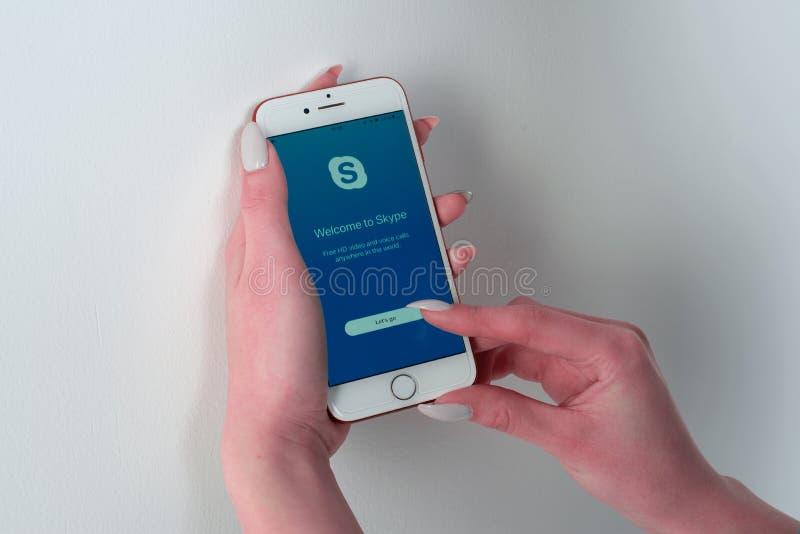Γυναίκα που χρησιμοποιεί τη Apple Iphone 8 κόκκινη παρουσιάζοντας σελίδα συμφωνίας Skype στοκ εικόνες