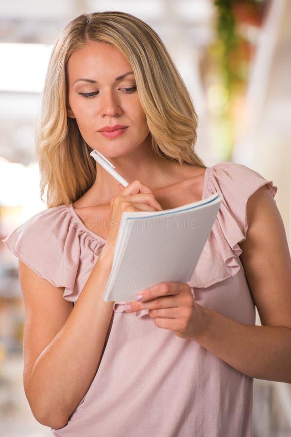 Γυναίκα που χρησιμοποιεί τον κατάλογο αγορών στο μανάβικο στοκ εικόνες
