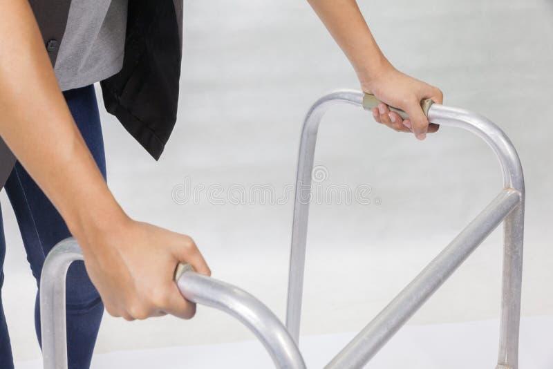 Γυναίκα που χρησιμοποιεί τον περιπατητή στο άσπρο υπόβαθρο στοκ φωτογραφίες
