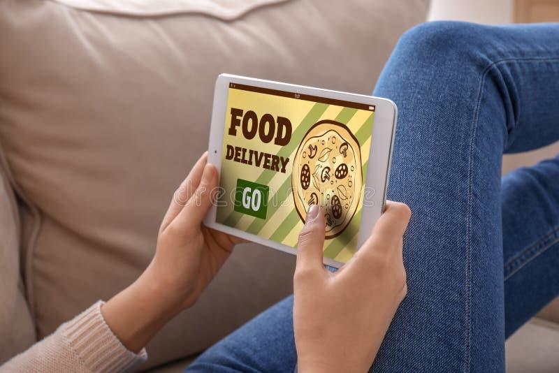 Γυναίκα που χρησιμοποιεί τον υπολογιστή ταμπλετών στην παράδοση τροφίμων διαταγής on-line στο σπίτι στοκ εικόνες