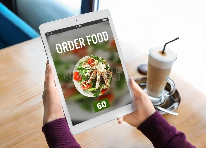 Γυναίκα που χρησιμοποιεί τον υπολογιστή ταμπλετών στην παράδοση τροφίμων διαταγής on-line στοκ φωτογραφία
