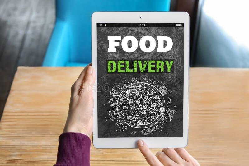 Γυναίκα που χρησιμοποιεί τον υπολογιστή ταμπλετών στην παράδοση τροφίμων διαταγής on-line στοκ εικόνες