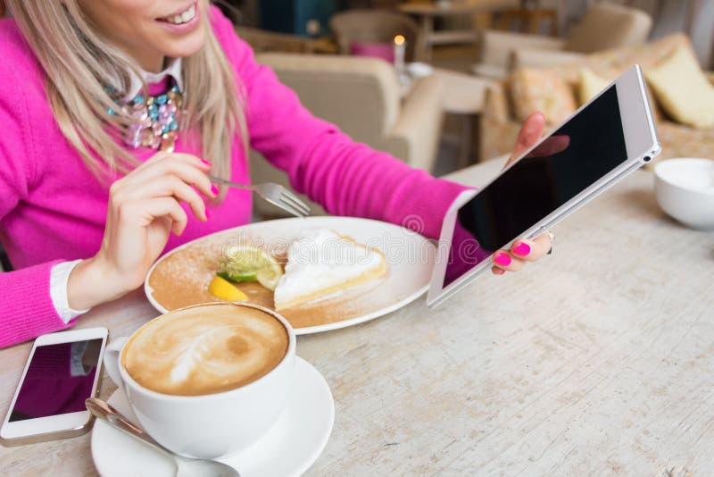 Γυναίκα που χρησιμοποιεί τον υπολογιστή ταμπλετών ενώ έχοντας το κέικ και τον καφέ στον καφέ στοκ φωτογραφία με δικαίωμα ελεύθερης χρήσης