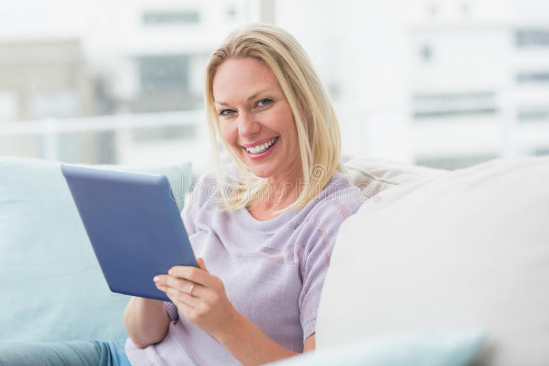 Γυναίκα που χρησιμοποιεί τον υπολογιστή ταμπλετών στον καναπέ στο σπίτι στοκ εικόνα με δικαίωμα ελεύθερης χρήσης