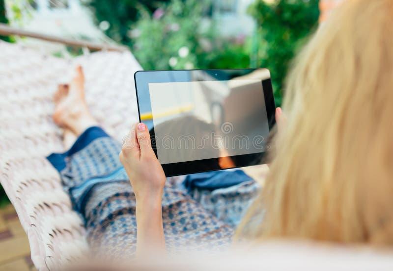 Γυναίκα που χρησιμοποιεί τον υπολογιστή ταμπλετών χαλαρώνοντας σε μια αιώρα στοκ εικόνες