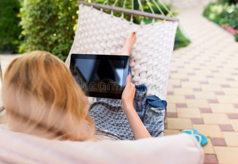 Γυναίκα που χρησιμοποιεί τον υπολογιστή ταμπλετών χαλαρώνοντας σε μια αιώρα στοκ εικόνα