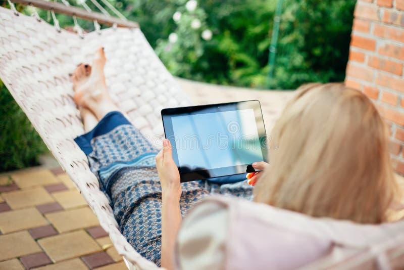 Γυναίκα που χρησιμοποιεί τον υπολογιστή ταμπλετών χαλαρώνοντας σε μια αιώρα στοκ φωτογραφία με δικαίωμα ελεύθερης χρήσης