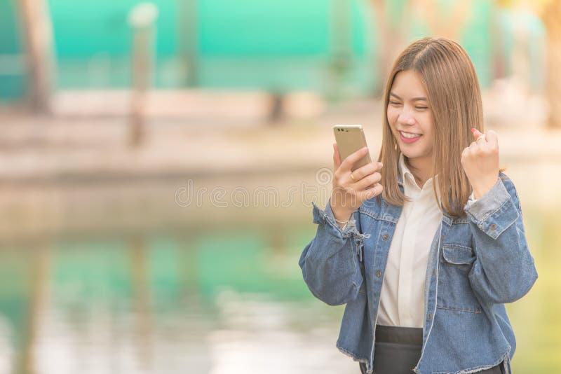 Γυναίκα που χρησιμοποιεί το έξυπνα τηλεφωνικά γέλιο και το χαμόγελο στοκ φωτογραφία με δικαίωμα ελεύθερης χρήσης