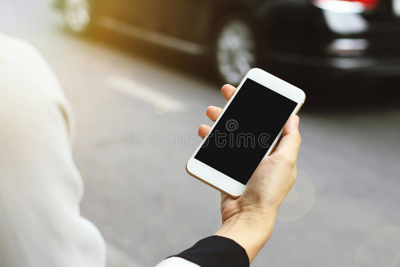Γυναίκα που χρησιμοποιεί το έξυπνο τηλέφωνο από την οδό, που χρησιμοποιεί την εφαρμογή υπηρεσιών ταξί στοκ φωτογραφία με δικαίωμα ελεύθερης χρήσης