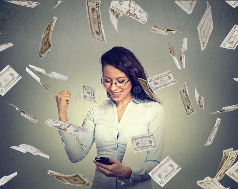 Γυναίκα που χρησιμοποιεί το έξυπνο τηλέφωνο που χτίζει τη σε απευθείας σύνδεση επιχείρηση που κάνουν τα δολάρια χρημάτων πέφτοντα στοκ φωτογραφίες