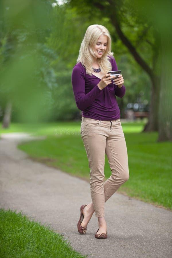Γυναίκα που χρησιμοποιεί το έξυπνο τηλέφωνο στο πάρκο στοκ φωτογραφίες με δικαίωμα ελεύθερης χρήσης