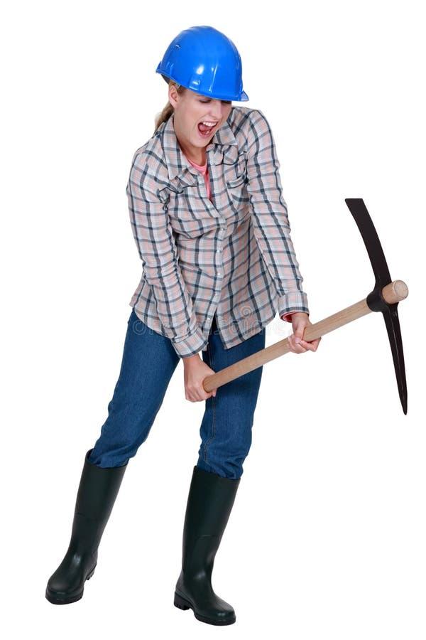 Γυναίκα που χρησιμοποιεί το επιλογή-τσεκούρι στοκ φωτογραφία
