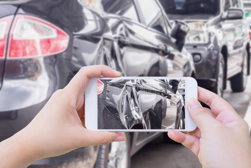 Γυναίκα που χρησιμοποιεί το κινητό έξυπνο τηλέφωνο που παίρνει τη φωτογραφία του αυτοκινήτου στοκ εικόνες