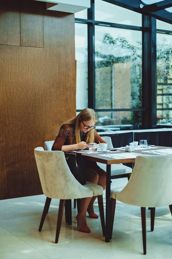 Γυναίκα που χρησιμοποιεί το κινητό τηλέφωνο καθμένος στο εστιατόριο στοκ εικόνες