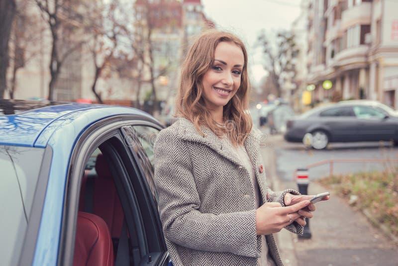 Γυναίκα που χρησιμοποιεί το κινητό τηλέφωνο που στέκεται εκτός από το αυτοκίνητό της στοκ φωτογραφία με δικαίωμα ελεύθερης χρήσης