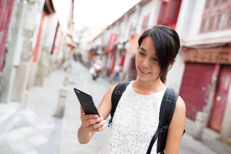 Γυναίκα που χρησιμοποιεί το κινητό τηλέφωνο σε Rua DA felicidade στοκ εικόνες με δικαίωμα ελεύθερης χρήσης