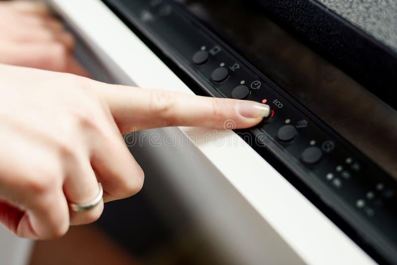 Γυναίκα που χρησιμοποιεί το πλυντήριο πιάτων στον τρόπο ενεργειακών αποταμιευτών στοκ φωτογραφία