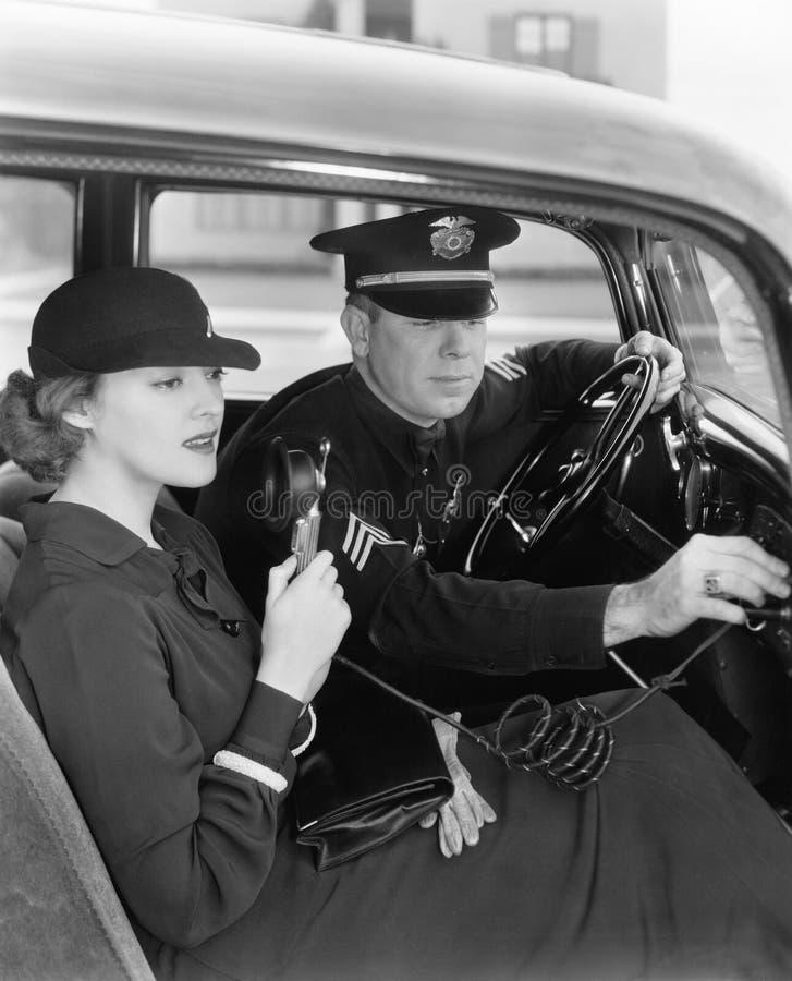 Γυναίκα που χρησιμοποιεί το ραδιόφωνο στο αυτοκίνητο με τον αστυνομικό (όλα τα πρόσωπα που απεικονίζονται δεν ζουν περισσότερο κα στοκ εικόνα με δικαίωμα ελεύθερης χρήσης