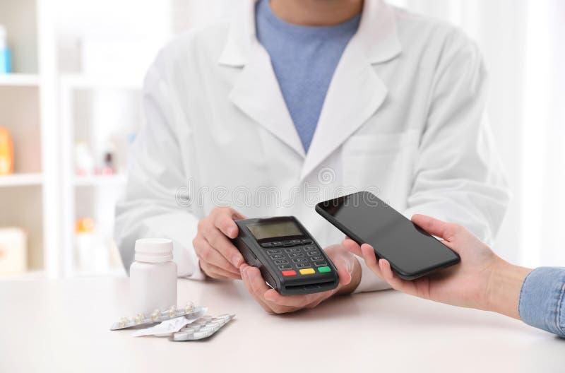 Γυναίκα που χρησιμοποιεί το τερματικό για την ανέπαφη πληρωμή με το smartphone στο φαρμακείο στοκ φωτογραφία με δικαίωμα ελεύθερης χρήσης