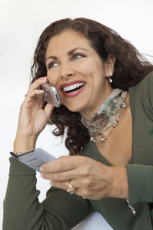 Γυναίκα που χρησιμοποιεί το τηλέφωνο κυττάρων και PDA στοκ φωτογραφία με δικαίωμα ελεύθερης χρήσης
