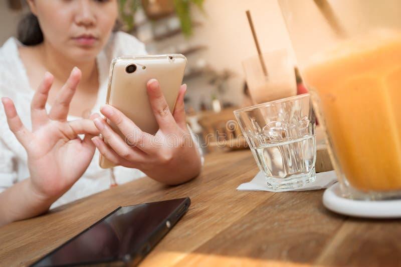 Γυναίκα που χρησιμοποιεί το τηλέφωνο στον καφέ στοκ φωτογραφία με δικαίωμα ελεύθερης χρήσης