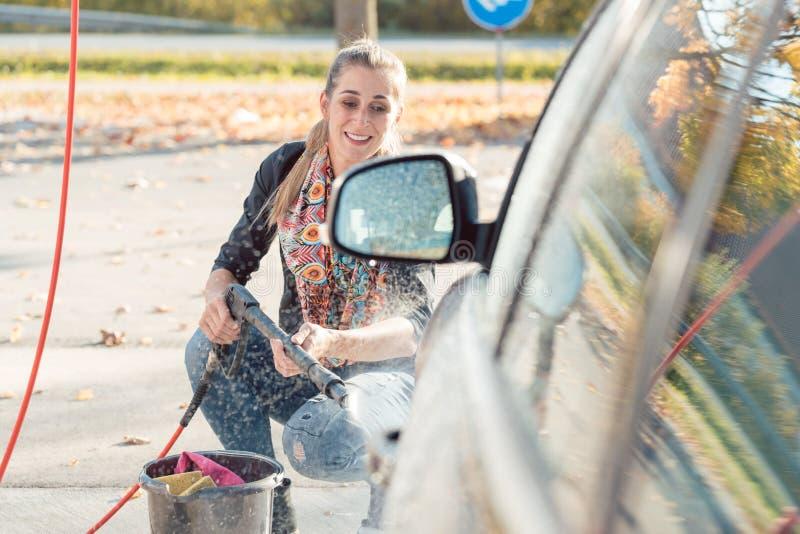 Γυναίκα που χρησιμοποιεί το υψηλό ακροφύσιο για να καθαρίσει το αυτοκίνητό της στοκ εικόνα με δικαίωμα ελεύθερης χρήσης