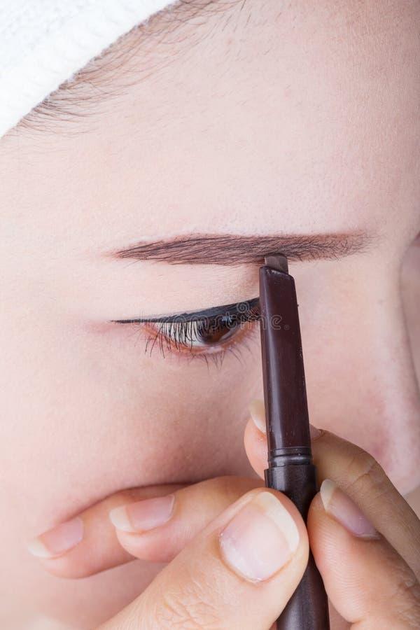 Γυναίκα που χρησιμοποιεί το φρύδι μολυβιών makeup στοκ φωτογραφίες