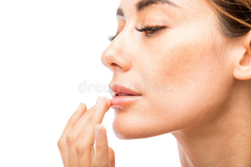 Γυναίκα που χρησιμοποιεί το χειλικό βάλσαμο στο στούντιο στοκ εικόνα