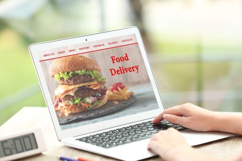 Γυναίκα που χρησιμοποιεί το lap-top στην παράδοση τροφίμων διαταγής στοκ εικόνα