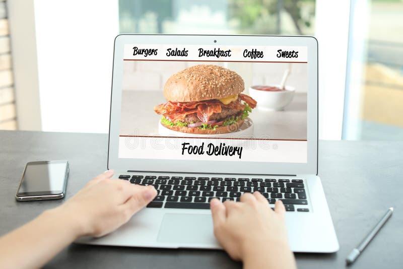 Γυναίκα που χρησιμοποιεί το lap-top στην παράδοση τροφίμων διαταγής στοκ εικόνες με δικαίωμα ελεύθερης χρήσης