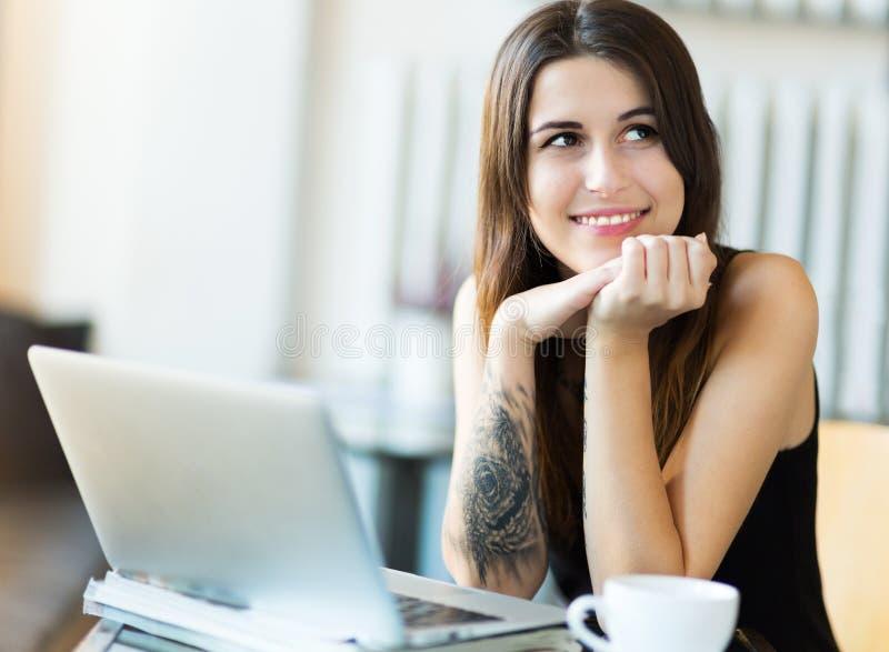 Γυναίκα που χρησιμοποιεί το lap-top στον καφέ στοκ φωτογραφία
