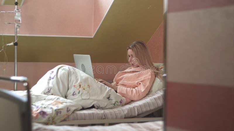 Γυναίκα που χρησιμοποιεί το lap-top στο νοσοκομειακό κρεβάτι στοκ φωτογραφίες με δικαίωμα ελεύθερης χρήσης