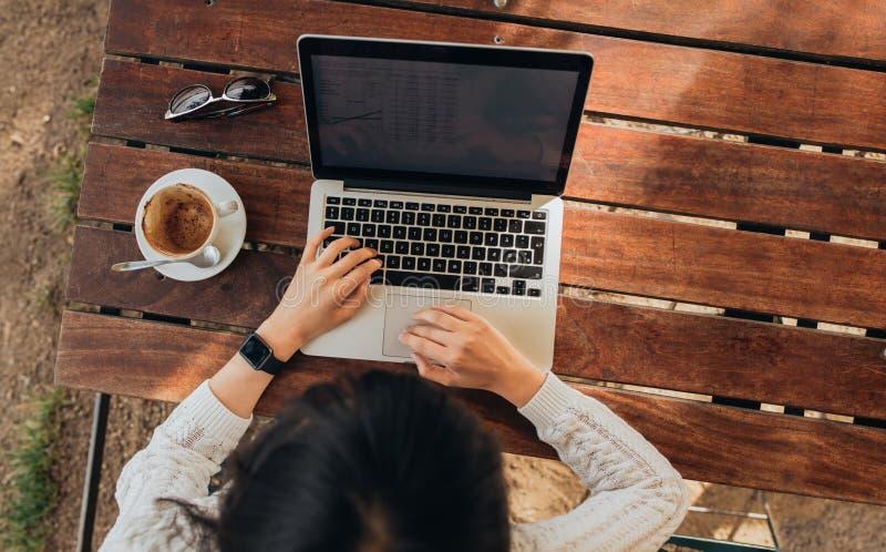 Γυναίκα που χρησιμοποιεί το lap-top της σε μια καφετερία στοκ φωτογραφίες