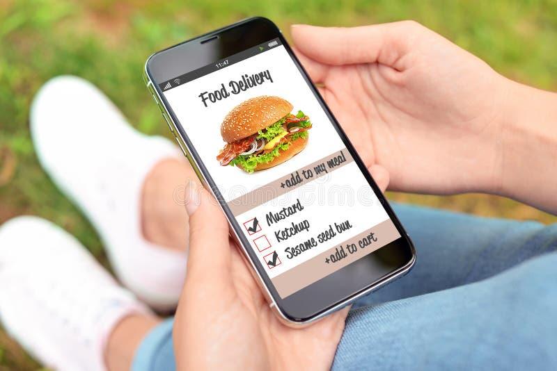 Γυναίκα που χρησιμοποιεί το smartphone στην παράδοση τροφίμων διαταγής στοκ φωτογραφία με δικαίωμα ελεύθερης χρήσης