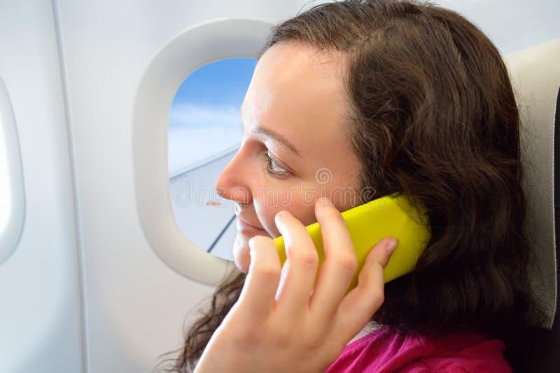 Γυναίκα που χρησιμοποιεί το smartphone στο αεροπλάνο στοκ εικόνες