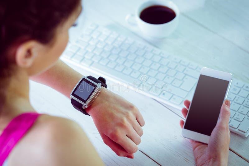 Γυναίκα που χρησιμοποιεί το smartwatch και το τηλέφωνό της στοκ εικόνες με δικαίωμα ελεύθερης χρήσης