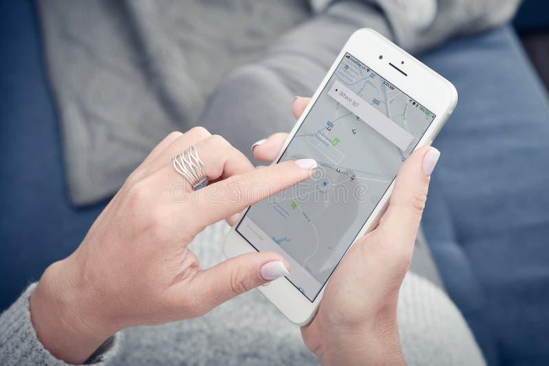 Γυναίκα που χρησιμοποιεί Uber app στο iPhone 8 της Apple συν στο σπίτι στοκ φωτογραφία με δικαίωμα ελεύθερης χρήσης